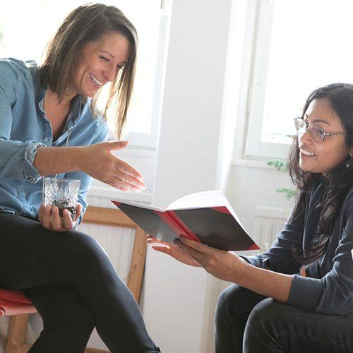 Två kvinnor som tittar i en skrivbok och diskuterar.